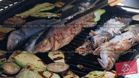 Купить «Cooking sea bass fish with vegetables on a grill barbecue», видеоролик № 33421759, снято 21 марта 2020 г. (c) Serg Zastavkin / Фотобанк Лори