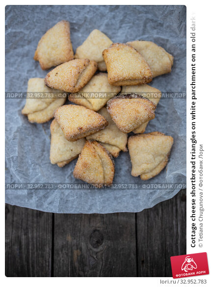 Cottage cheese shortbread triangles on white parchment on an old dark wooden background. Стоковое фото, фотограф Tetiana Chugunova / Фотобанк Лори