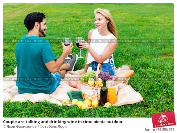 Couple are talking and drinking wine in time picnic outdoor. Стоковое фото, фотограф Яков Филимонов / Фотобанк Лори
