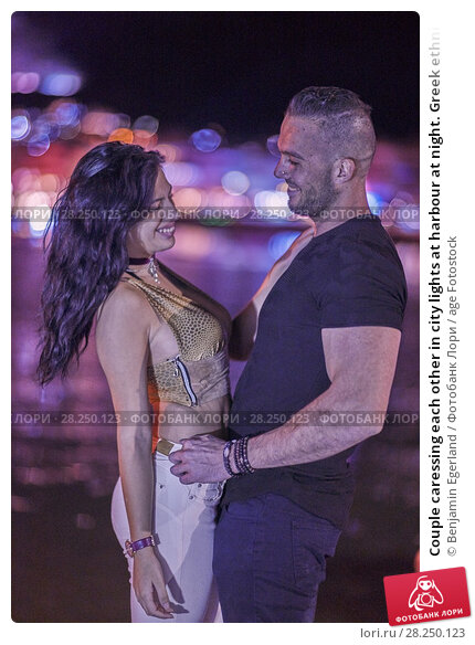 Купить «Couple caressing each other in city lights at harbour at night. Greek ethnicity. In Hersonissos, Crete, Greece.», фото № 28250123, снято 16 сентября 2017 г. (c) age Fotostock / Фотобанк Лори