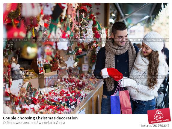 Купить «Couple choosing Christmas decoration», фото № 26760647, снято 22 ноября 2017 г. (c) Яков Филимонов / Фотобанк Лори