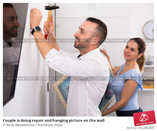 Купить «Couple is doing repair and hanging picture on the wall», фото № 29240827, снято 19 октября 2017 г. (c) Яков Филимонов / Фотобанк Лори