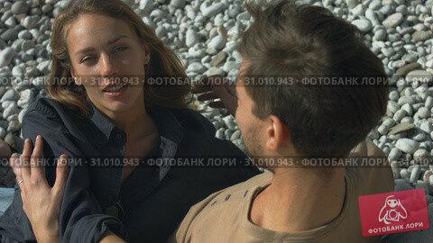 Couple is hugging sitting on the beach. Стоковое видео, видеограф Denis Mishchenko / Фотобанк Лори