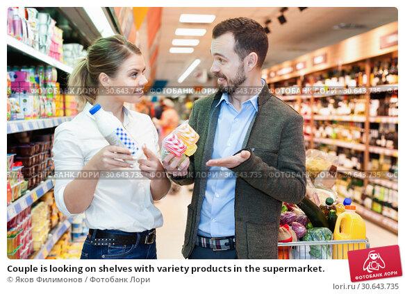 Купить «Couple is looking on shelves with variety products in the supermarket.», фото № 30643735, снято 4 апреля 2018 г. (c) Яков Филимонов / Фотобанк Лори