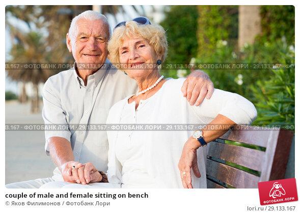 Купить «couple of male and female sitting on bench», фото № 29133167, снято 16 августа 2017 г. (c) Яков Филимонов / Фотобанк Лори
