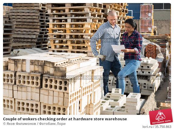 Couple of wokers checking order at hardware store warehouse. Стоковое фото, фотограф Яков Филимонов / Фотобанк Лори
