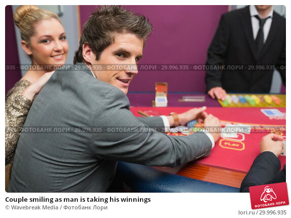 Купить «Couple smiling as man is taking his winnings», фото № 29996935, снято 20 июля 2012 г. (c) Wavebreak Media / Фотобанк Лори
