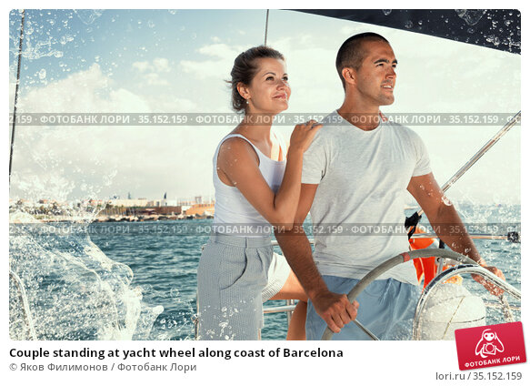 Couple standing at yacht wheel along coast of Barcelona. Стоковое фото, фотограф Яков Филимонов / Фотобанк Лори