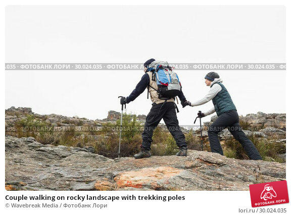 Купить «Couple walking on rocky landscape with trekking poles», фото № 30024035, снято 21 августа 2013 г. (c) Wavebreak Media / Фотобанк Лори