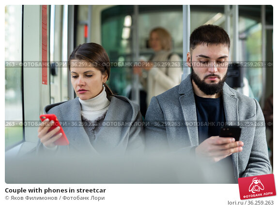Couple with phones in streetcar. Стоковое фото, фотограф Яков Филимонов / Фотобанк Лори
