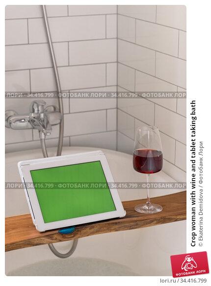Crop woman with wine and tablet taking bath. Стоковое фото, фотограф Ekaterina Demidova / Фотобанк Лори