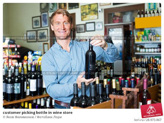 Купить «customer picking bottle in wine store», фото № 28973867, снято 19 июня 2019 г. (c) Яков Филимонов / Фотобанк Лори