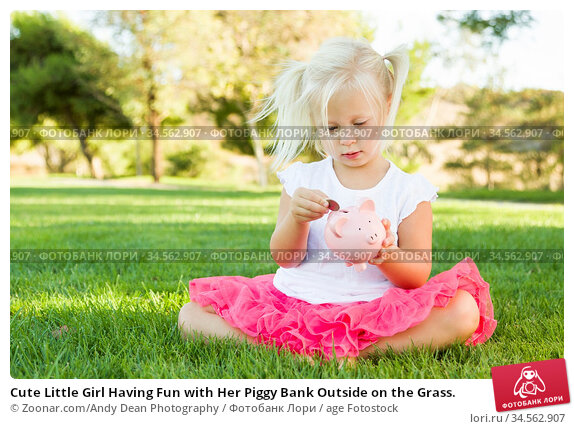 Cute Little Girl Having Fun with Her Piggy Bank Outside on the Grass. Стоковое фото, фотограф Zoonar.com/Andy Dean Photography / age Fotostock / Фотобанк Лори