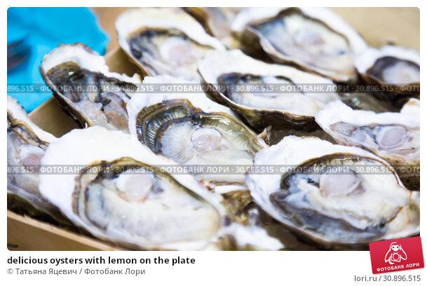 Купить «delicious oysters with lemon on the plate», фото № 30896515, снято 6 октября 2016 г. (c) Татьяна Яцевич / Фотобанк Лори