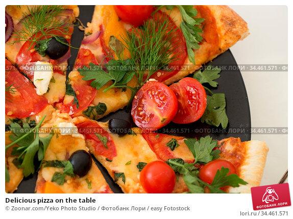 Delicious pizza on the table. Стоковое фото, фотограф Zoonar.com/Yeko Photo Studio / easy Fotostock / Фотобанк Лори