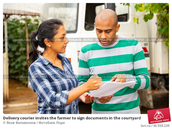Delivery courier invites the farmer to sign documents in the courtyard. Стоковое фото, фотограф Яков Филимонов / Фотобанк Лори