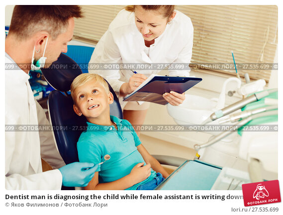 Купить «Dentist man is diagnosing the child while female assistant is writing down patient's complaint», фото № 27535699, снято 25 мая 2017 г. (c) Яков Филимонов / Фотобанк Лори