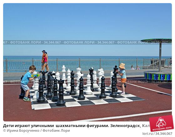 Дети играют уличными  шахматными фигурами. Зеленоградск, Калининградская область. Редакционное фото, фотограф Ирина Борсученко / Фотобанк Лори