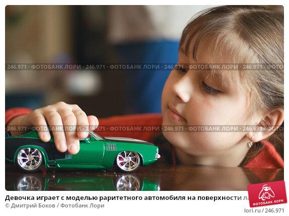 Девочка играет с моделью раритетного автомобиля на поверхности лакированного стола, фото № 246971, снято 6 мая 2006 г. (c) Дмитрий Боков / Фотобанк Лори