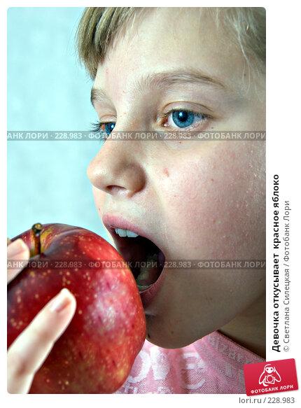 Девочка откусывает  красное яблоко, фото № 228983, снято 18 февраля 2008 г. (c) Светлана Силецкая / Фотобанк Лори