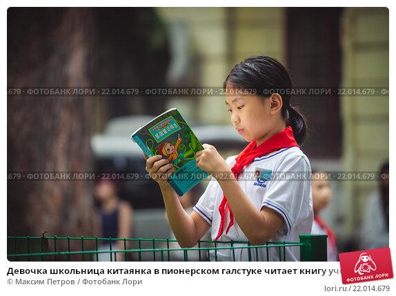 Девочка школьница китаянка в пионерском галстуке читает книгу учебник в парке в Гуанчжоу, фото № 22014679, снято 6 ноября 2015 г. (c) Максим Петров / Фотобанк Лори