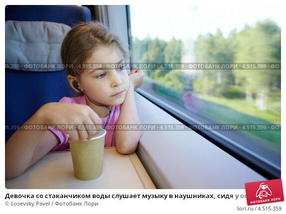 Купить «Девочка со стаканчиком воды слушает музыку в наушниках, сидя у окна движущегося скоростного поезда», фото № 4515359, снято 19 июля 2011 г. (c) Losevsky Pavel / Фотобанк Лори