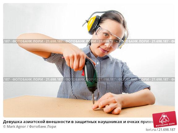 Купить «Девушка азиатской внешности в защитных наушниках и очках применяет дрель», фото № 21698187, снято 20 января 2016 г. (c) Mark Agnor / Фотобанк Лори