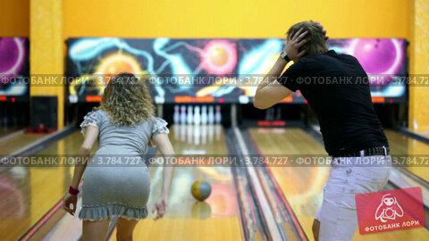 Купить «Девушка бросает шар для боулинга и сбивает кегли, парень прыгает от радости», видеоролик № 3784727, снято 28 марта 2012 г. (c) Losevsky Pavel / Фотобанк Лори