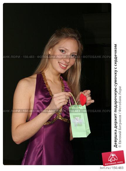 Купить «Девушка держит подарочную сумочку с сердечком», фото № 150483, снято 23 марта 2018 г. (c) Евгений Батраков / Фотобанк Лори