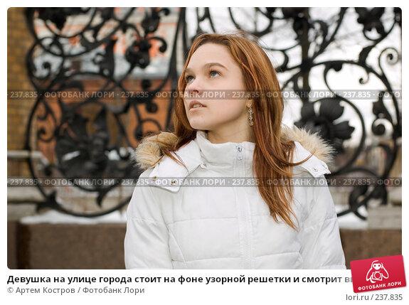 Девушка на улице города стоит на фоне узорной решетки и смотрит вверх, фото № 237835, снято 28 марта 2008 г. (c) Артем Костров / Фотобанк Лори