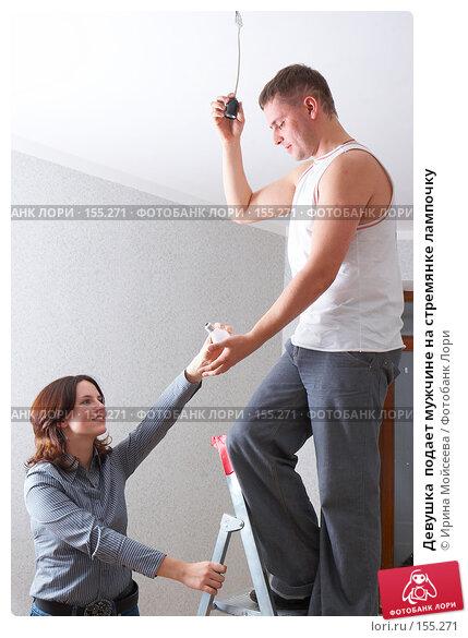Девушка  подает мужчине на стремянке лампочку, фото № 155271, снято 5 декабря 2007 г. (c) Ирина Мойсеева / Фотобанк Лори