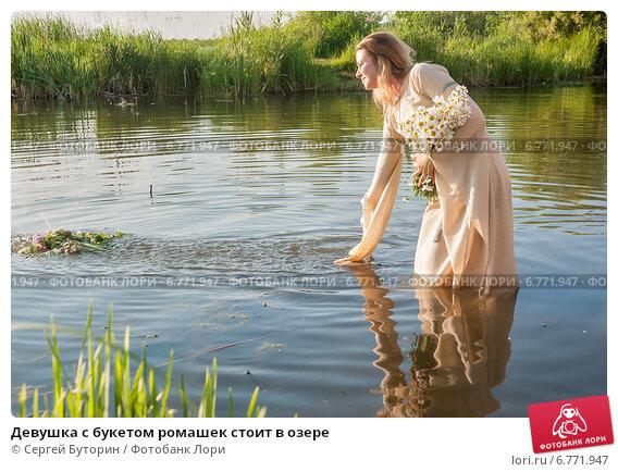 Купить «Девушка с букетом ромашек стоит в озере», фото № 6771947, снято 9 июля 2014 г. (c) Сергей Буторин / Фотобанк Лори