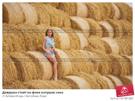 Купить «Девушка стоит на фоне катушек сена», фото № 10787083, снято 16 августа 2015 г. (c) Литвяк Игорь / Фотобанк Лори