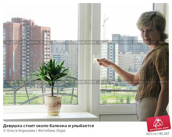 Девушка стоит около балкона и улыбается, эксклюзивное фото № 45247, снято 21 мая 2007 г. (c) Ольга Хорькова / Фотобанк Лори