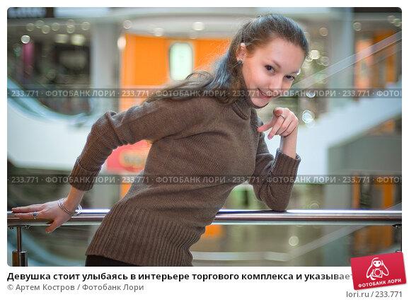 Девушка стоит улыбаясь в интерьере торгового комплекса и указывает пальцем, фото № 233771, снято 5 марта 2008 г. (c) Артем Костров / Фотобанк Лори