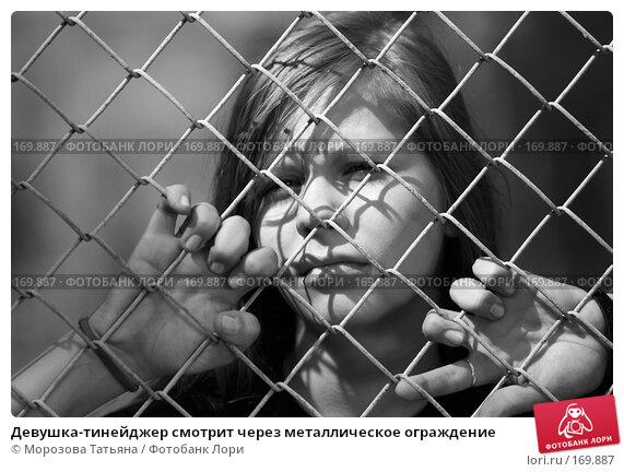 Купить «Девушка-тинейджер смотрит через металлическое ограждение», фото № 169887, снято 21 июля 2007 г. (c) Морозова Татьяна / Фотобанк Лори