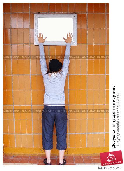 Купить «Девушка, тянущаяся к картине», фото № 995243, снято 17 октября 2018 г. (c) Эдуард Жлобо / Фотобанк Лори