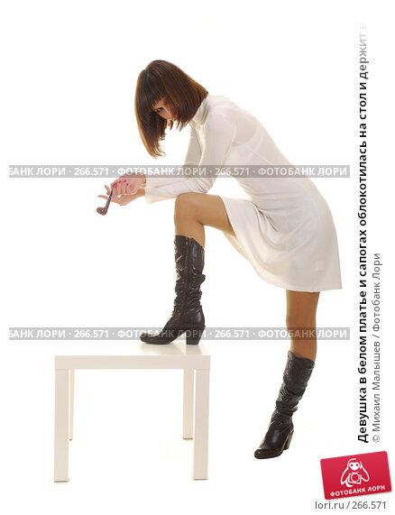 Девушка в белом платье и сапогах облокотилась на стол и держит в руках трубку, фото № 266571, снято 19 января 2008 г. (c) Михаил Малышев / Фотобанк Лори