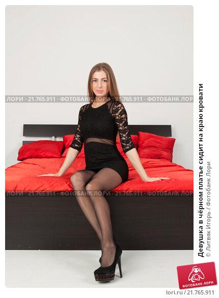 русская девушка в чёрном платье на кровати