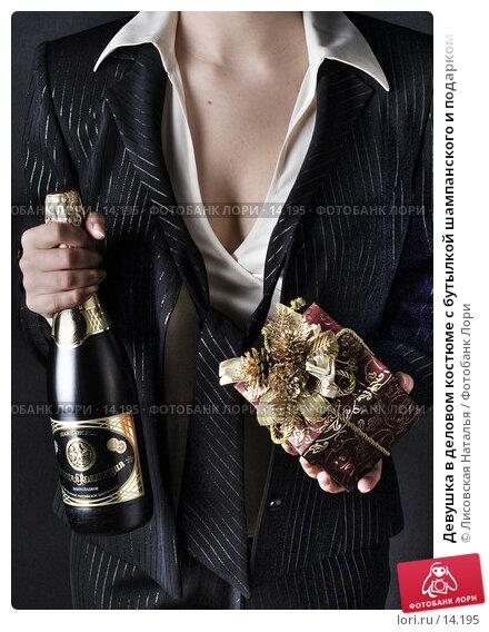 Девушка в деловом костюме с бутылкой шампанского и подарком, фото № 14195, снято 6 декабря 2006 г. (c) Лисовская Наталья / Фотобанк Лори