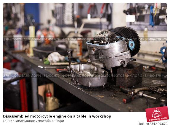 Disassembled motorcycle engine on a table in workshop. Стоковое фото, фотограф Яков Филимонов / Фотобанк Лори