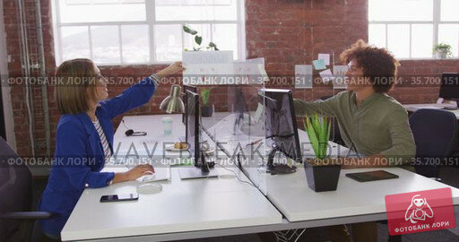 Diverse male and female business colleagues sitting at desks with sneeze guard passing document. Стоковое видео, агентство Wavebreak Media / Фотобанк Лори