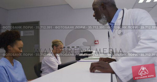 Diverse male doctor coming to hospital reception and talking to female staff. Стоковое видео, агентство Wavebreak Media / Фотобанк Лори