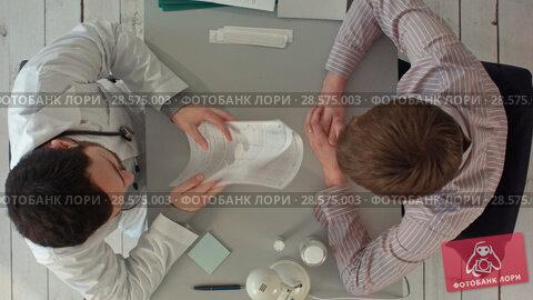 Купить «Doctor discussing a patient's results. Top view», видеоролик № 28575003, снято 28 ноября 2015 г. (c) Vasily Alexandrovich Gronskiy / Фотобанк Лори