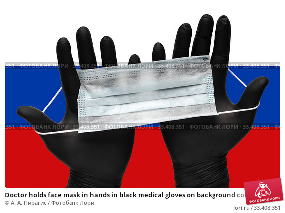 Doctor holds face mask in hands in black medical gloves on background colors flag of Russia or Russian flag. Pandemic insurance coronavirus. Стоковое фото, фотограф А. А. Пирагис / Фотобанк Лори