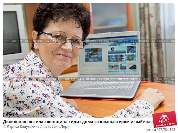 Купить «Довольная пожилая женщина сидит дома за компьютером и выбирает маршруты для будущих путешествий», фото № 27734303, снято 4 февраля 2018 г. (c) Лариса Капусткина / Фотобанк Лори