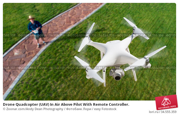 Drone Quadcopter (UAV) In Air Above Pilot With Remote Controller. Стоковое фото, фотограф Zoonar.com/Andy Dean Photography / easy Fotostock / Фотобанк Лори