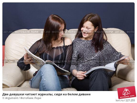 Две девушки читают журналы, сидя на белом диване, фото № 227255, снято 13 марта 2008 г. (c) Argument / Фотобанк Лори