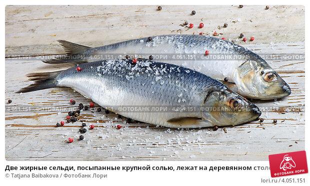 Купить «Две жирные сельди, посыпанные крупной солью, лежат на деревянном столе», фото № 4051151, снято 29 января 2012 г. (c) Tatjana Baibakova / Фотобанк Лори