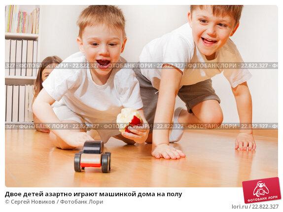 Купить «Двое детей азартно играют машинкой дома на полу», фото № 22822327, снято 3 апреля 2016 г. (c) Сергей Новиков / Фотобанк Лори